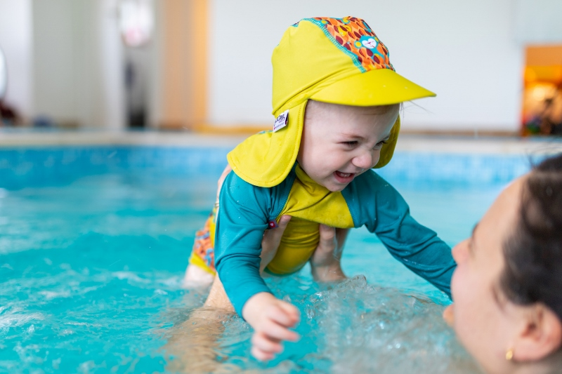 Toddler in pool with hat and rash vest