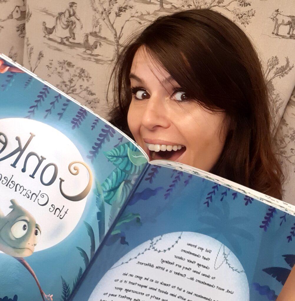 Hannah Peckham holds Conker the Chameleon book
