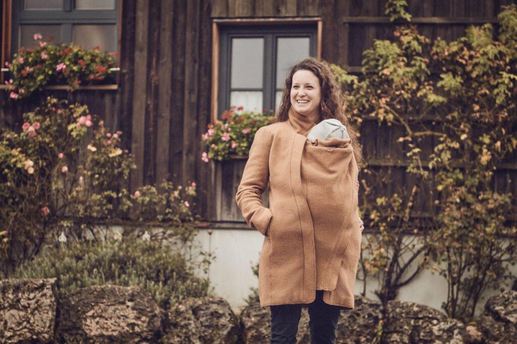 Mamalila Oslo Babywearing coat, lifestyle of woman wearing baby on her front